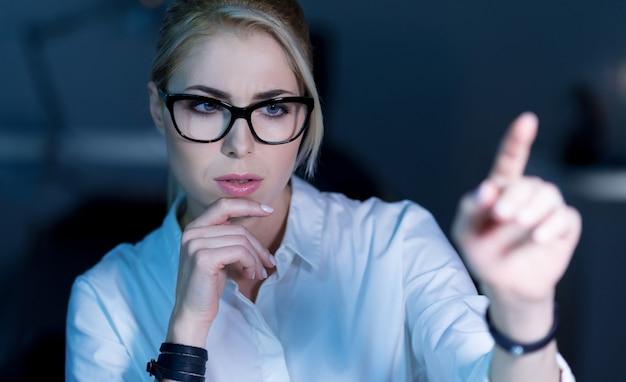 탈출구 찾기. 영재 집중된 숙련 된 it 여성이 사무실에 앉아 정보를 해독하는 동안 미래 기술을 사용합니다.