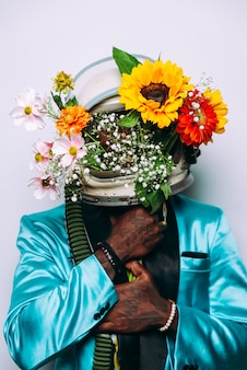 우주 헬멧과 꽃 구성을 착용하는 남자와 미술 개념 프리미엄 사진