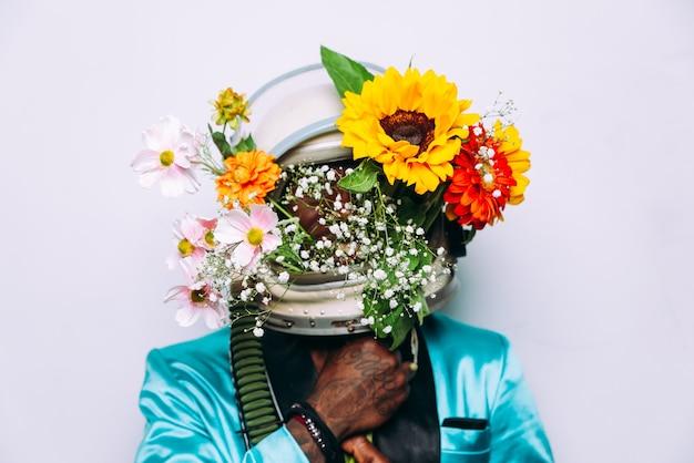우주 헬멧과 꽃 구성을 착용하는 남자와 미술 개념