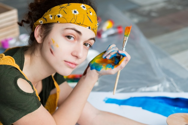 Fine art hobby. portrait of beautiful female painter, lying down on floor, creating abstract artwork.