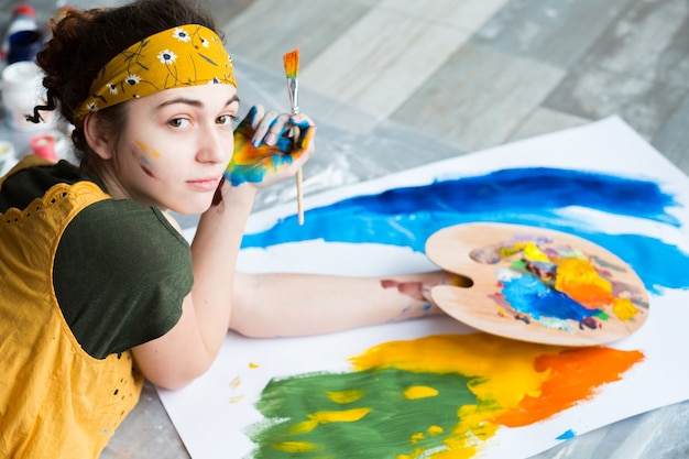 Fine art hobby. top view of talented female painter, lying down on floor, creating abstract artwork.