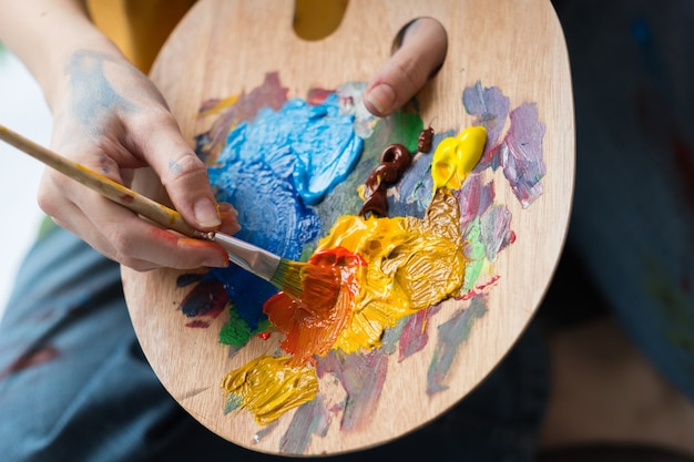 Fine art school. closeup of artist hands holding wooden palette, mixing acrylic paint with brush.