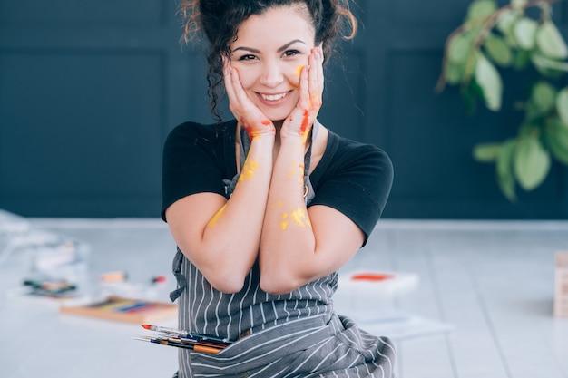 美術学校。床に座って、興奮している幸せな女性。カラフルなペンキで顔や手が汚れています。