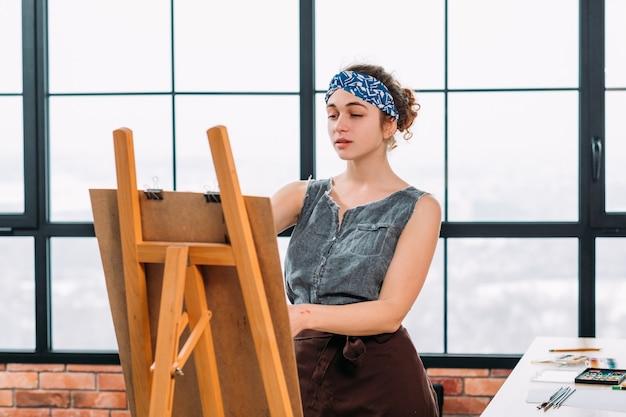 美術学校。イーゼルを使用して、現代のワークショップでアートワークを作成するインスピレーションを得た女性画家