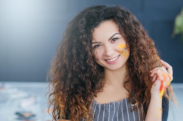 美術学校。巻き毛のきれいな女性の肖像画。カラフルなペンキで顔や手が汚れています。