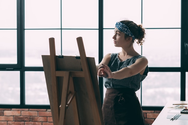 Fine art school. young lady learning how to paint, using easel