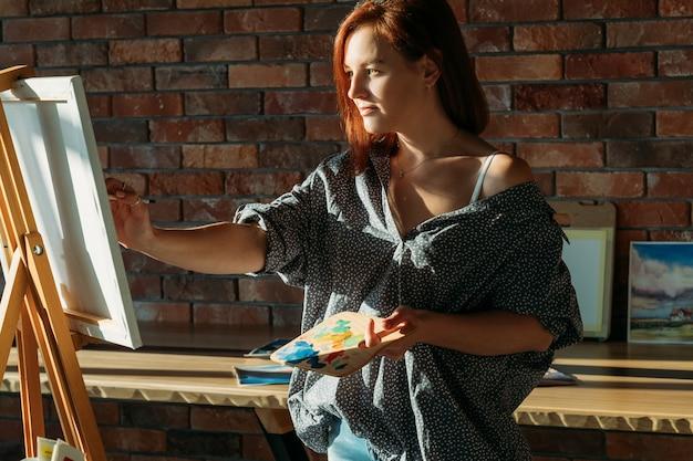 仕事で素晴らしいアーティスト。スタジオアートワーク。キャンバスに木製パレットを描いた思いやりのある赤毛の女性。