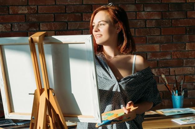 仕事で素晴らしいアーティスト。スタジオのインスピレーション。キャンバスに木製パレットを描いた思いやりのある赤毛の女性。