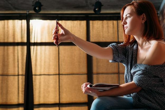 ファインアーティストのスケッチ。スタジオワークスペース。スケッチブックを保持している仮想オブジェクトを測定する女性画家。
