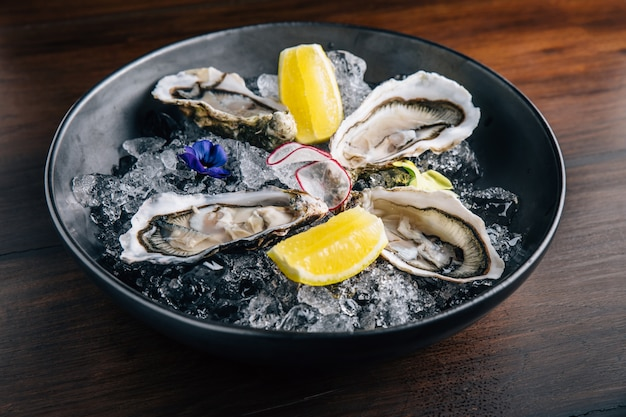 Fine de claire oyster and lemon served in black bowl with ice on wooden table.