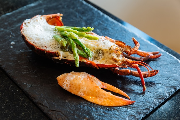 Fine dining: lobster meat and claw with foam topping with asparagus served on stone plate.