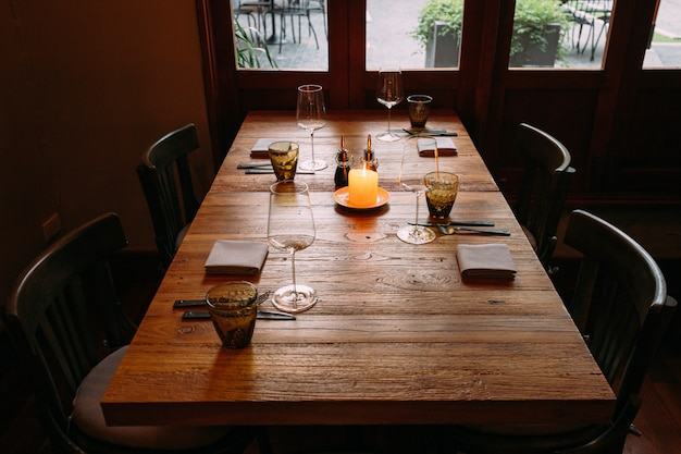 Fine dining wooden table with cutleries, wine glasses, napkins, naperies and lighted candle on the table.