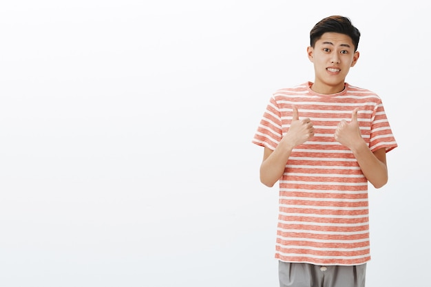 Fine i guess. portrait of unsure awkward young attractive asian man in striped t-shirt making tight ucertain smile and showing thumbs up gesture as if agree or like idea