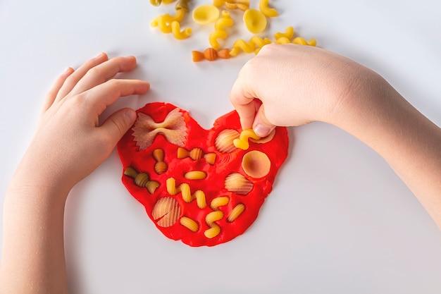 細かい運動技能。子供の創造性。家庭での子供の発達のための塑像用粘土モデリング。子供の手は、モデリングのために生地からハートを作成します。ドライパスタを使ったアンチストレスゲーム