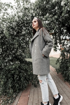 Fine portrait young woman in vintage bandana in fashionable gray coat near green foliage in park. cute girl model in trendy clothes walks and enjoys beauty nature. pretty fashion lady.