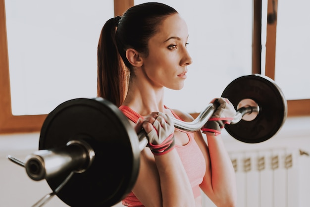 Fine sportswoman is exercising in gym alone