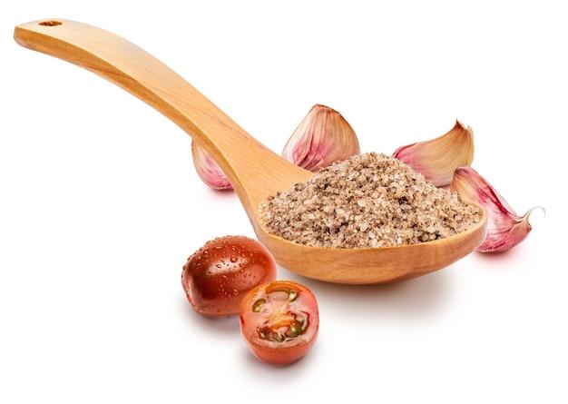 Соль мелкая белая с помидорами и чесноком в деревянной ложке (сборник сортов соли).