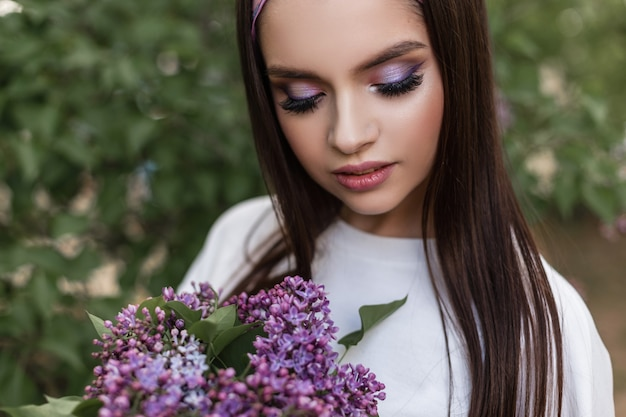 公園の緑の葉の近くに立っている花束シックな紫色の花とカラーメイクでファッショナブルな白い服を着たバンダナの立派な女性。かわいい女の子は花束を見て、美しさと香りのライラックを楽しんでいます