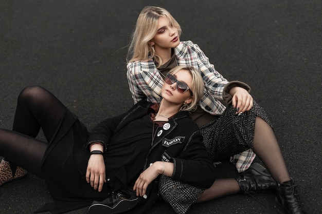 Fine young woman in black clothes in sunglasses lies on asphalt next to blonde girlfriend in checkered blazer