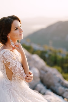 Fineart destination wedding photo in montenegro mount lovchen the bride on top of the mountain plays