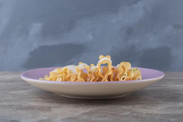 Мелко нарезанные листы моркови и лазаньи с йогуртом на тарелке, на мраморной поверхности.