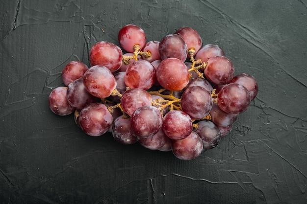 최고의 천연 가정 포도 세트, 짙은 붉은 과일, 검은 돌 배경, 평면도