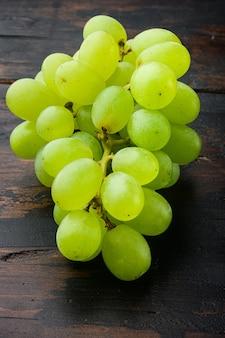 오래된 어두운 나무 탁자에 있는 최고의 천연 가정 포도 세트, 녹색 과일