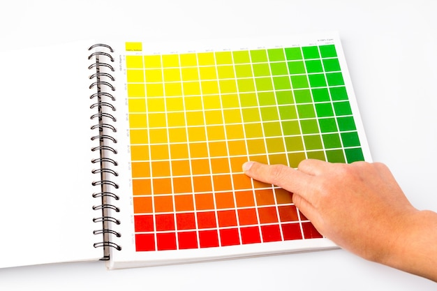 Finger are pointing at the selected color channel, color book is an important tool to use as a sample color in a variety of jobs such as design, printing, etc. in order to control the quality of work.