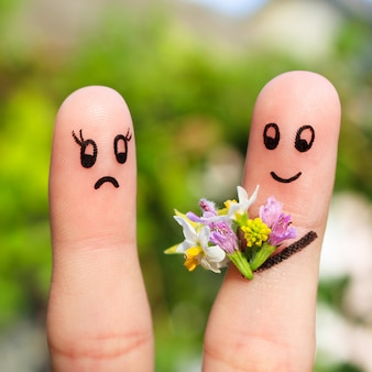 Finger art of couple. man gives a woman a bouquet of flowers