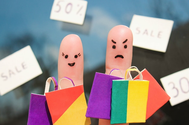 Finger art of couple with shopping bags. man is unhappy