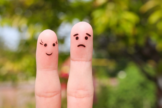 Finger art of couple. woman is cheerful, man is sad.