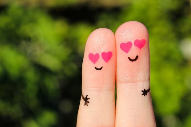 幸せなカップルの指アート。男と女が目の中にピンクのハートを抱き締めます。