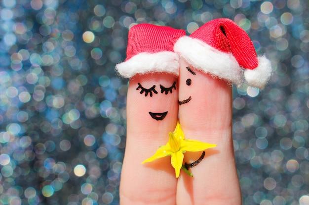幸せなカップルの指アートはクリスマスを祝います。男性は女性に花をあげています。