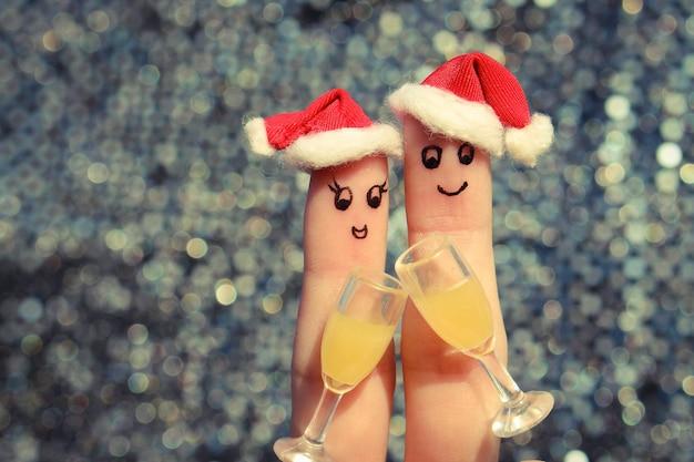 Искусство пальца счастливой пары в новогодних шапках.