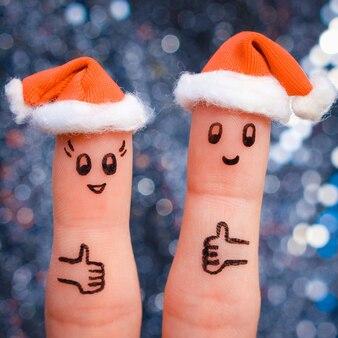 Искусство пальца пары празднует рождество. концепция мужчины и женщины, смеясь в новогодних шапках. счастливая пара показывает палец вверх. тонированное изображение.