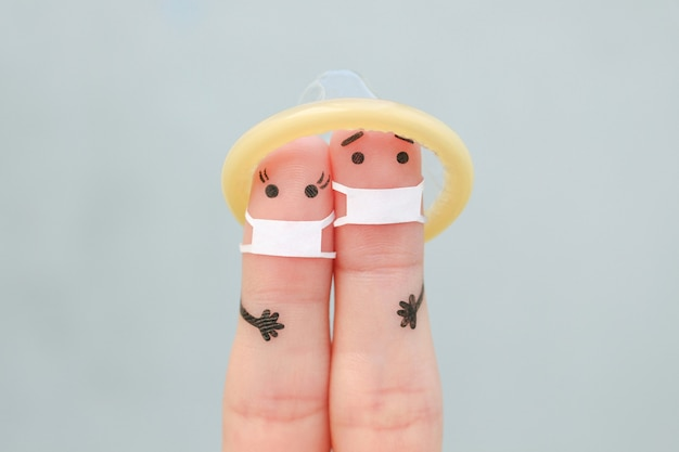 Пальцевое искусство пары в медицинских масках и презервативе