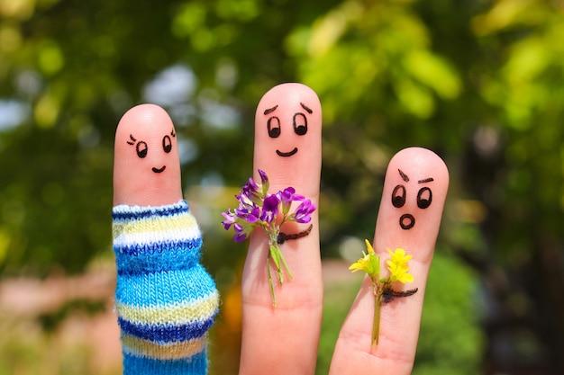 행복한 커플의 손가락 예술. 남자는 꽃 임신 한 여자를주고있다. 다른 소년은 질투하고 화가납니다.