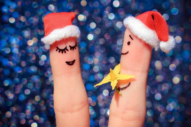 幸せなカップルの指アート。男性は女性に花をあげています