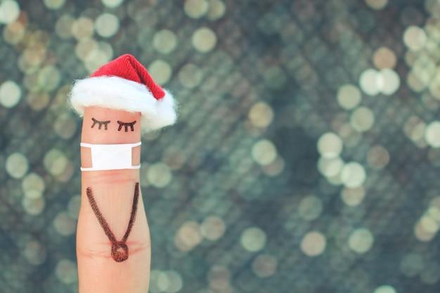 Пальцевое искусство одинокой женщины в медицинской маске от covid-2019. люди концепции празднуют рождество в новогодней шапке.