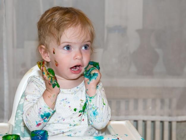 아이들을 위한 손가락 색칠. 어린 소녀는 종이에 손으로 물감을 그립니다. 어린이 발달 개념.