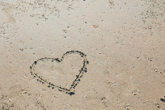 Finger drawn heart love symbol on sea beach sand holiday summer concept