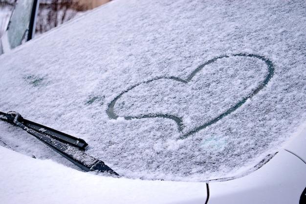 車の雪に覆われたフロントガラスに指で描かれたハート。バレンタインデーのコンセプト。