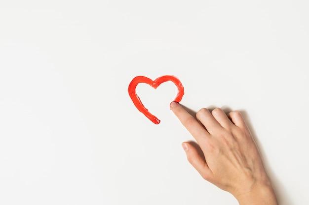 指は赤いペンキでハートの形を描きます。慈善、愛または聖バレンタインの日の概念。