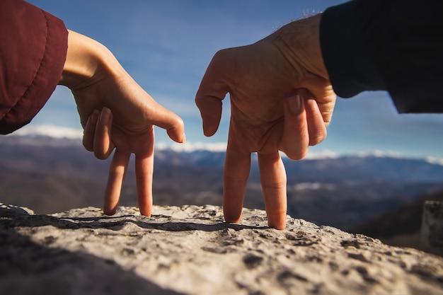 손가락 제스처 남자와 여자는 손을 잡고 눈 덮인 산을 봅니다.