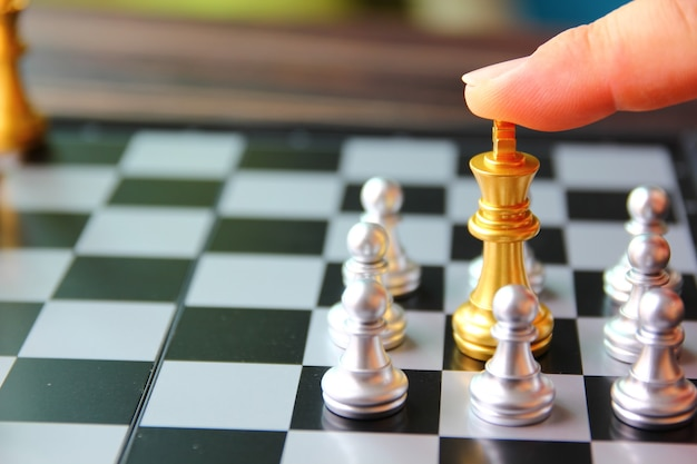 The finger on golden king chess between silver chess on chess board