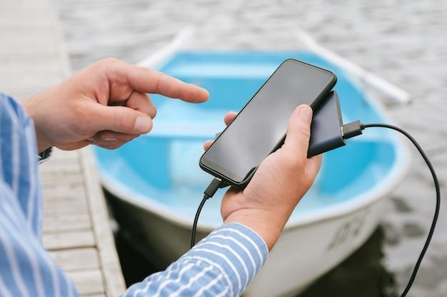 스마트폰 화면 앞에 있는 손가락, 전원 은행에서 충전, 손에 들고. 물과 부두에 보트를 배경으로.