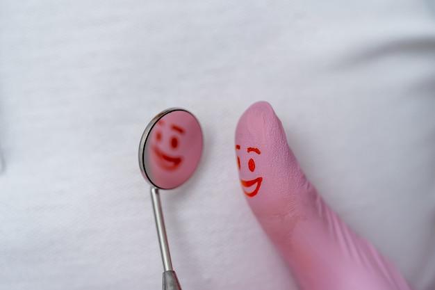 Палец в розовых перчатках с красной улыбкой на нем. глядя в зеркало дантиста.