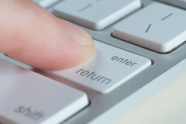 指はコンピューターのキーボードのenterキーを押します。