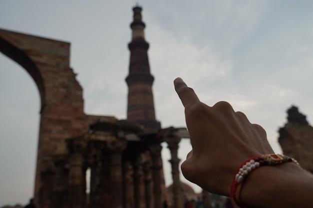 指はクトゥブミナールのビューを示しています-クトゥブミナールロード、デリー画像旅行画像
