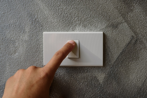 Finger is turning on or off on light switch.